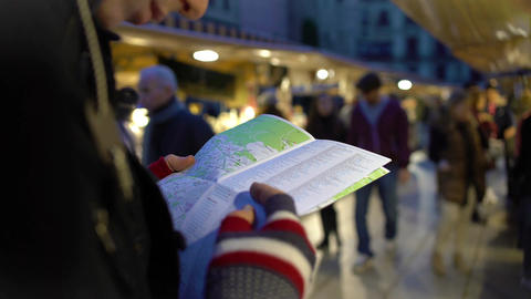 Traveller holding city map in hands, looking at souvenir shops, checking route Footage