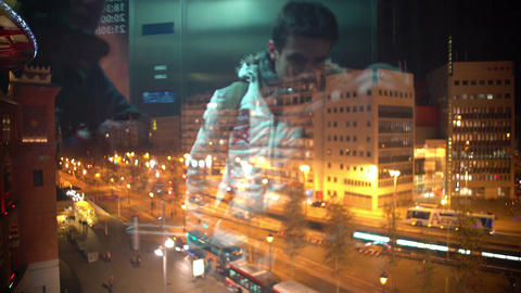Reflection of young men using glass elevator at shopping mall, night city life Footage