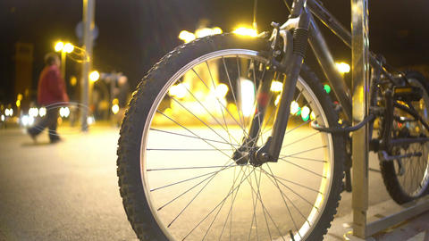 Defocused night city lights and pedestrians seen through bicycle wheel spokes Footage