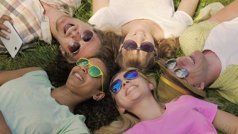 Multiethnic group of friends relaxing on grass in park, laughing, having fun Live Action