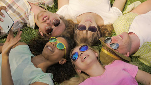 Best friends having good rest, lying on grass, joking and laughing, friendship Footage