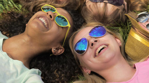 Close-up of friends faces, happy girls and guys lying on grass, joking, laughing Footage