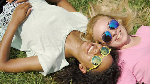 Two female friends lying on grass, gossiping about guys and smiling, friendship Live Action