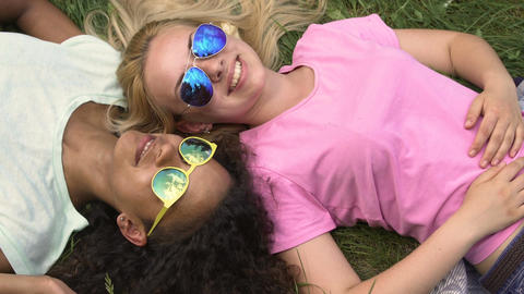 Young women relaxing on lawn and enjoying weekend, best friends hanging out Footage