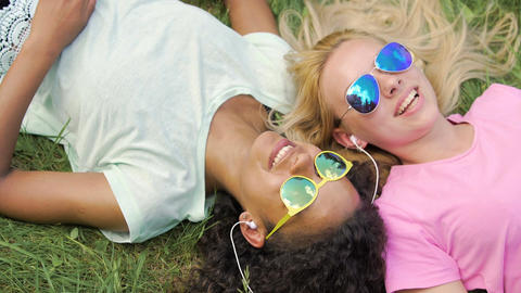 Two beautiful girls lying on grass, listening to music and singing song together Footage