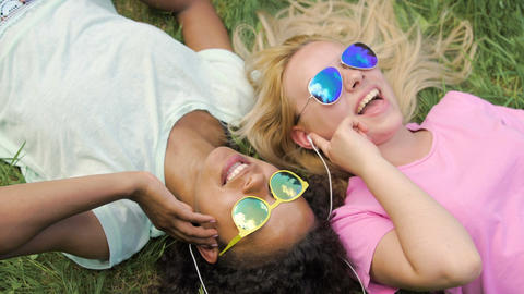 Two beautiful women listening to music in headphones and singing, lying on grass Footage