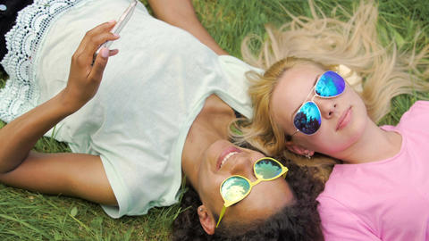 Two girls best friends lying on lawn, taking photos on cellphone, fun in park Footage