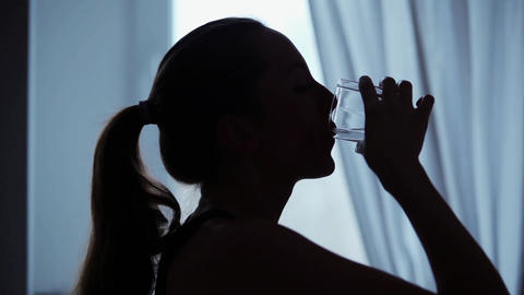 Woman drinks a glass of water Footage