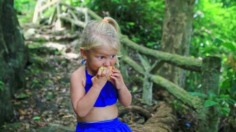 Closeup Little Blond Girl Eats Large Apple in Jungle Footage