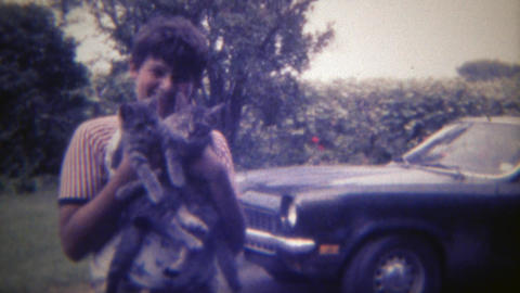 1969: Boy holding 2 lost kitty cats that he found with his camero car. DES MOINE Footage