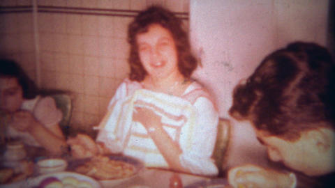 1963: Italian family eating spaghetti pasta dinner at packed kitchen table. BUFF Footage