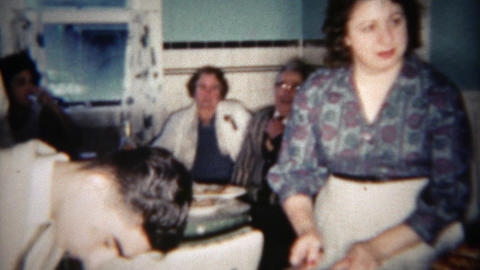 1963: Young jewish mother preparing meal for family guests in kitchen. BUFFALO,  Footage