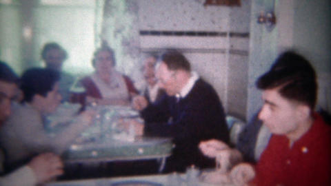 1963: Large family crowded into kitchen dining table for holiday feast. BUFFALO, Footage