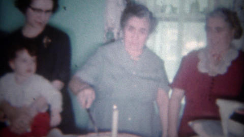 1963: Grandma cuts in giant round birthday cake as friend helps blow out candle. Footage