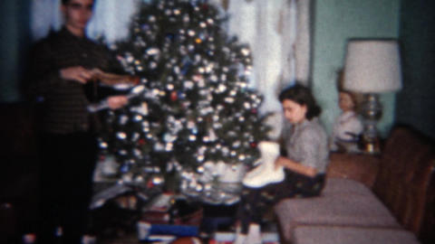 1962: Siblings get ice skates for holiday gift in front of Christmas tree. BUFFA Footage