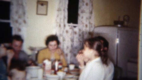 1962: Family cozy at kitchen table enjoying late night snack. BUFFALO, NEW YORK Footage