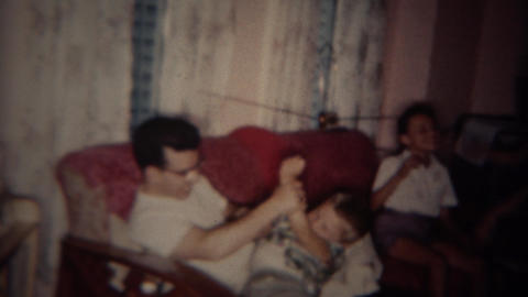 1962: Entire family play punching and fighting in tv watching room. BUFFALO, NEW Footage