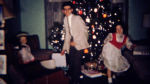1961: Brother sister show off twist dancing skills in front of Christmas tree. B Footage