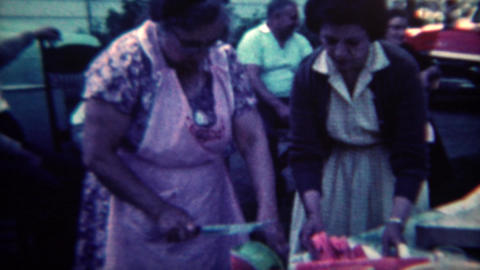 1961: Grandma slicing watermelon for summer picnic festival event. CINCINNATI, O Footage