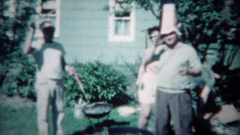 1961: Man gets dounce man grilling outdoor from sassy wife and drunk buddy. CINC Footage