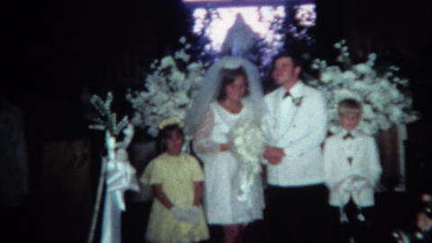1966: Newly married couple posing with wedding party. CINCINNATI, OHIO Footage