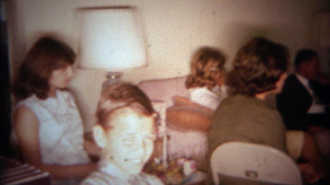 1966: American family celebrates thanksgiving in the kitchen and watching tv. BU Footage