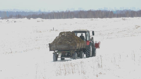 Tractor with trailer rides on snow field Footage