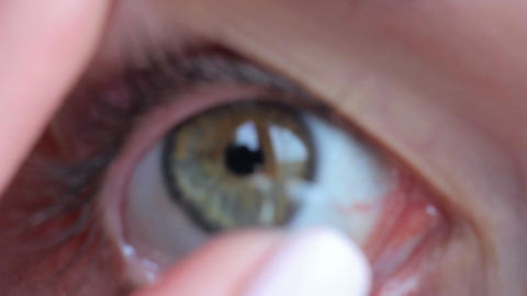 Macro filming contact lens wear insert in the eye, green eye of brunette girl, h Footage