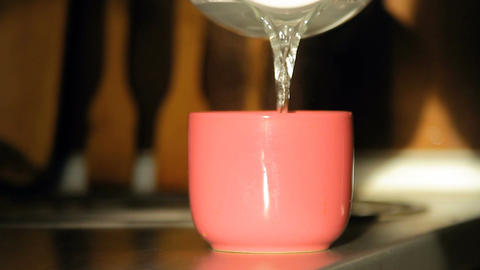 Boiling water is poured into a pink cup Footage