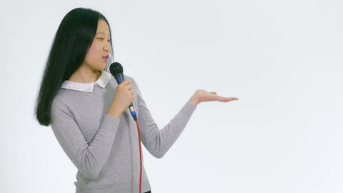 Teenage Asian girl holding mic showing product 1 Live影片