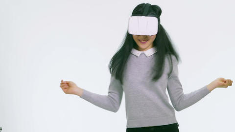 Teenage Asian girl wearing VR goggles dancing happily 1 Filmmaterial