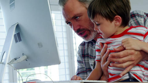 Father and son using desktop pc Live Action