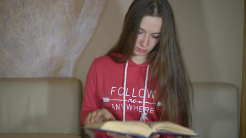 Woman Reading A Book She Throws Out The Book And Begins To Play On Gamepad Footage
