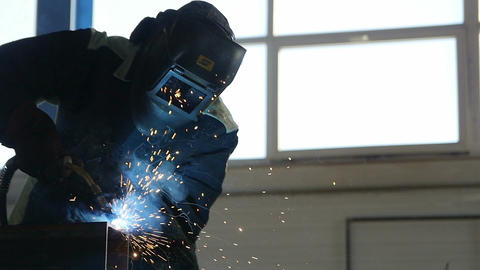 Welder in Mask and Protective Suit Works against Window Footage