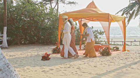 Bride and Groom Bypass Purifying Fire at Canopy on Beach Footage