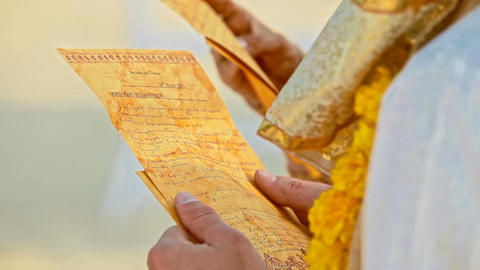 Closeup Golden Sheets with Vows in Newlyweds Hands Footage