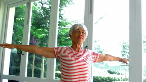 Senior woman performing stretching exercise on fitness ball Footage
