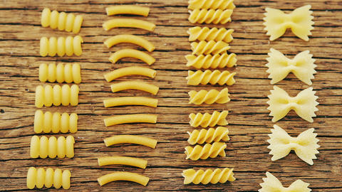 Various pasta aligned vertically on wooden table background Footage