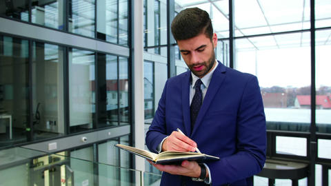 Businessman writing in diary at office Footage