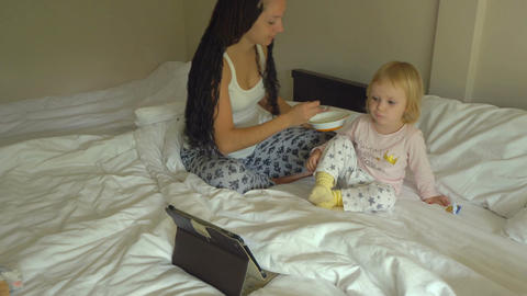 Beautiful young woman feeding little baby girl porridge while looking on tablet Footage