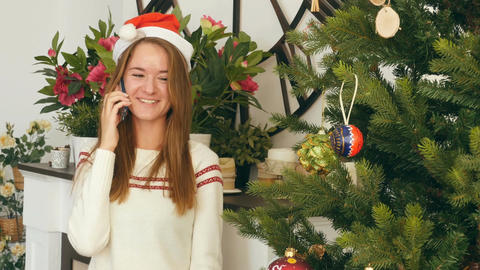 Smiling girl in red christmas cap talking on the phone nearby Christmas tree Footage
