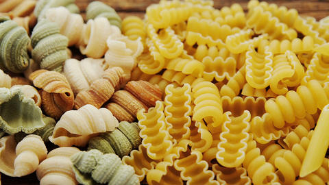 Various pasta in different colour on wooden table Footage