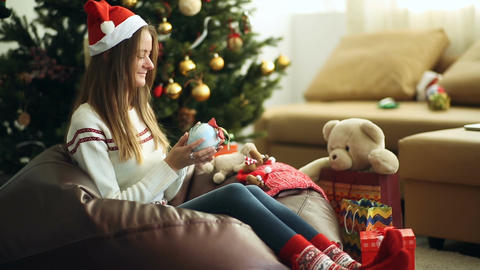 Young beautiful girl wraps a Christmas gift Footage