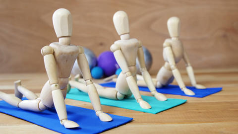 Wooden figurine exercising on exercise mat in front of gym balls against wooden background Live Action
