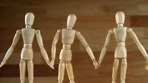 Wooden figurines representing businesspeople holding hands Footage
