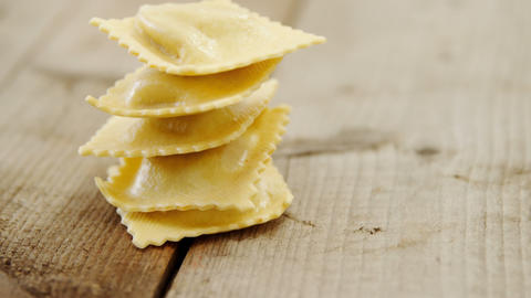 Pyramid of five homemade ravioli pasta on wooden background Footage