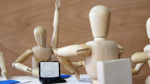 Wooden figurines having meeting in conference room in office on wooden Footage