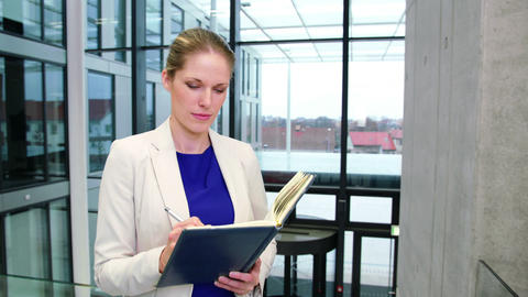 Businesswoman writing in diary at office Footage
