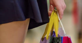 Close-up of girl holds in hand shopping sale bags HD video. Legs woman shopper Footage