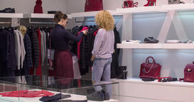 Women shopping at clothing store boutique HD video. Girl looks wear, manager Footage